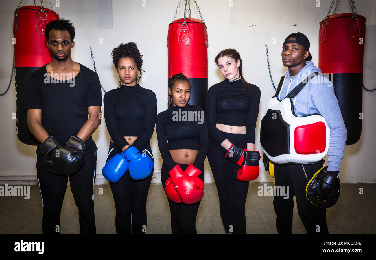 Portrait of four young determined boxers and their experienced trainer - Stock Image