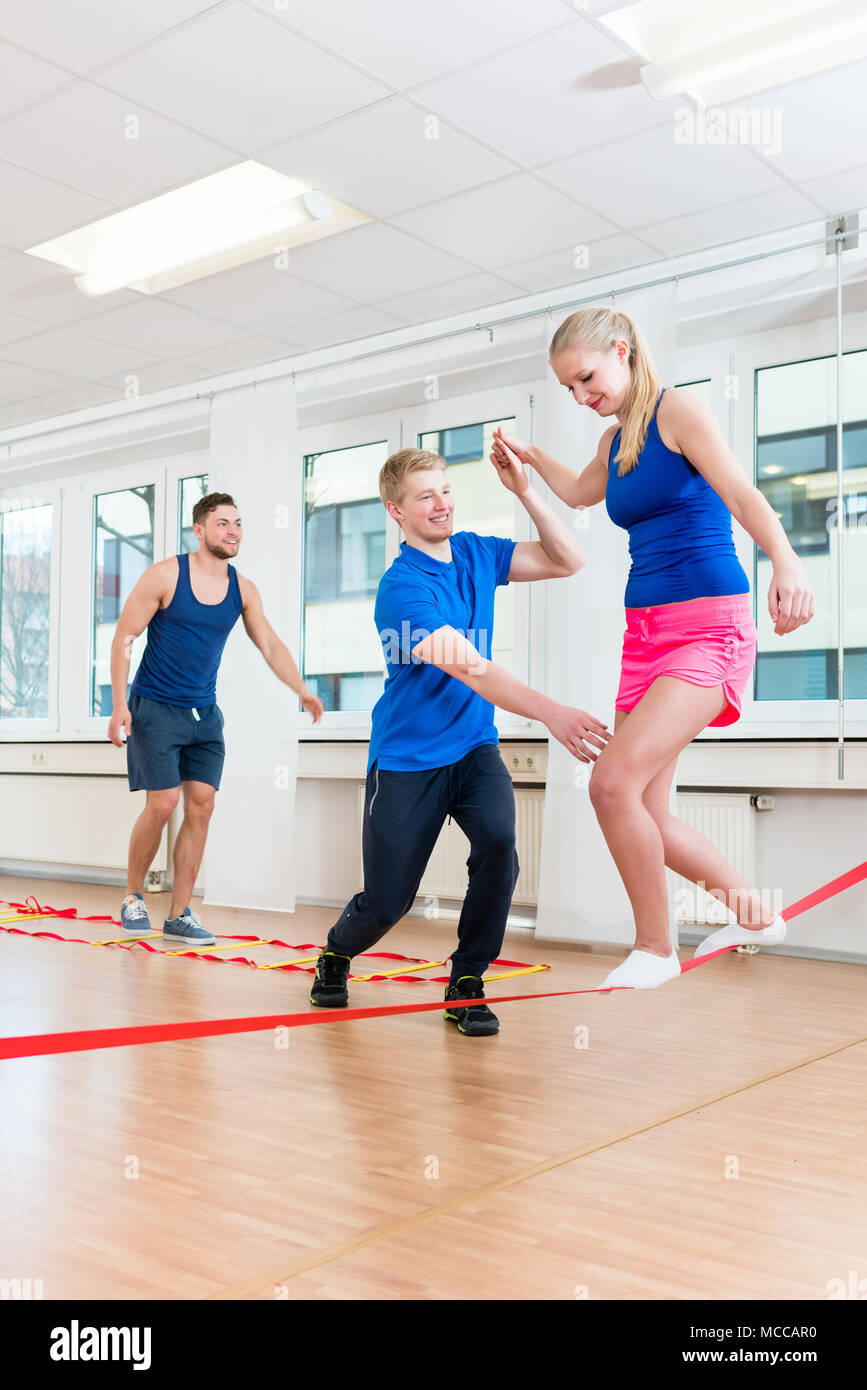 Physio practicing slacklining with athletes in gym - Stock Image