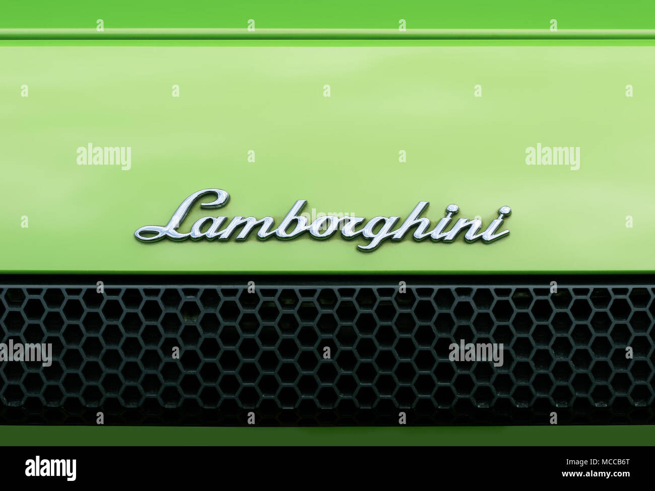 Closeup detail of a Lamborghini badge logo branding emblem and the Lamborghini text font on the rear of a lime green Lamborghini Murcielago. - Stock Image