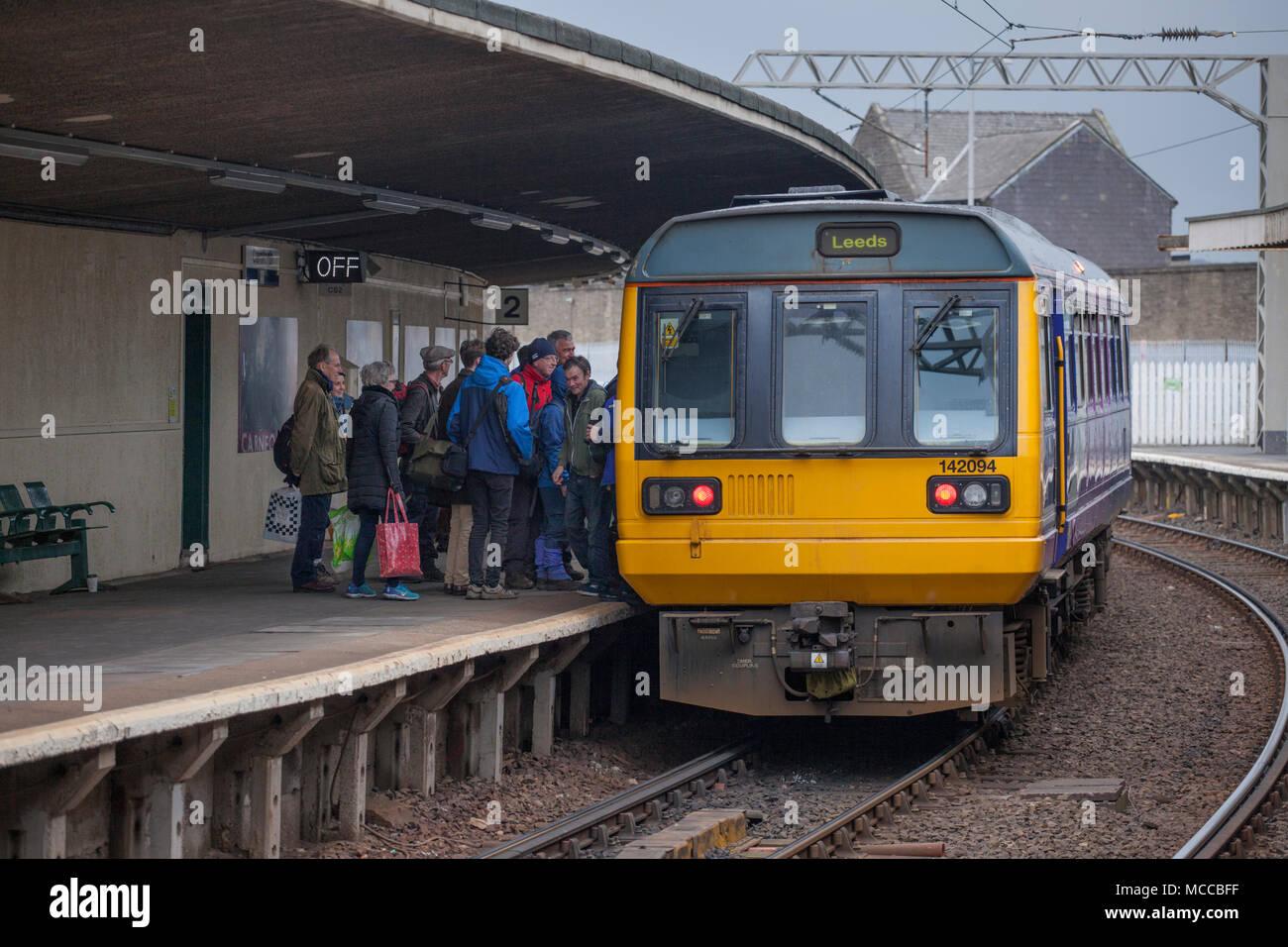 Passengers boarding a Northern Rail pacer train at Carnforth railway station - Stock Image