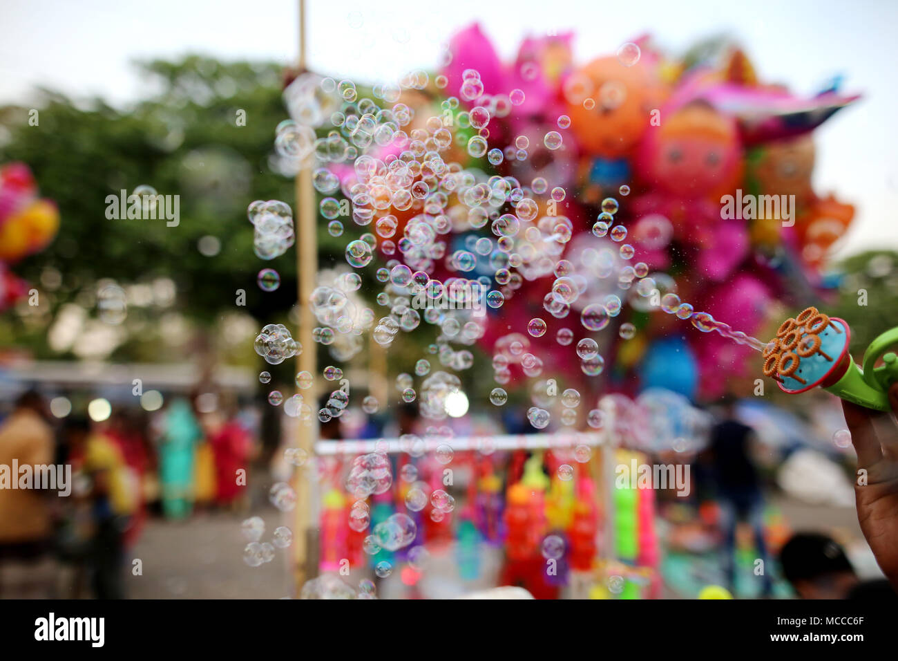 Dhaka, Bangladesh. A bubble seller is making bubbles to attract his customer specially children in Dhaka, Bangladesh on April 15, 2018. Bangladesh has made remarkable progress in reducing poverty, supported by sustained economic growth. Based on the international poverty line of $1.90 per person per day, it reduced poverty from 44.2 percent in 1991 to 13.8 percent in 2016/17 according to World Bank. © Rehman Asad/Alamy Stock Photo - Stock Image