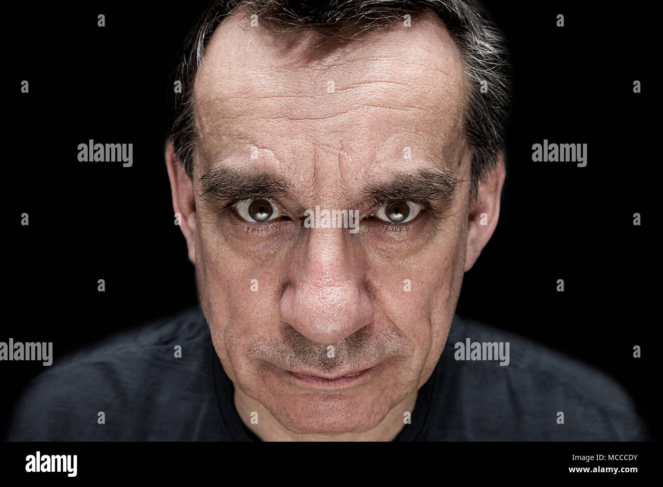 Dramatic high contrast portrait of angry menacing man - Stock Image