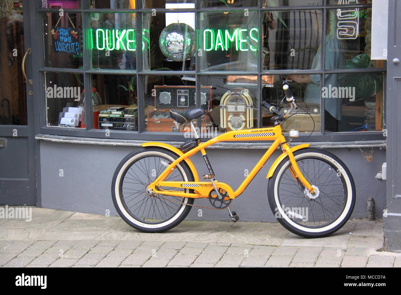 Yellow bicycle propped up against the Black Dog Hair Cutters Salon in Falmouth, Cornwall, England, UK, PETER GRANT Stock Photo