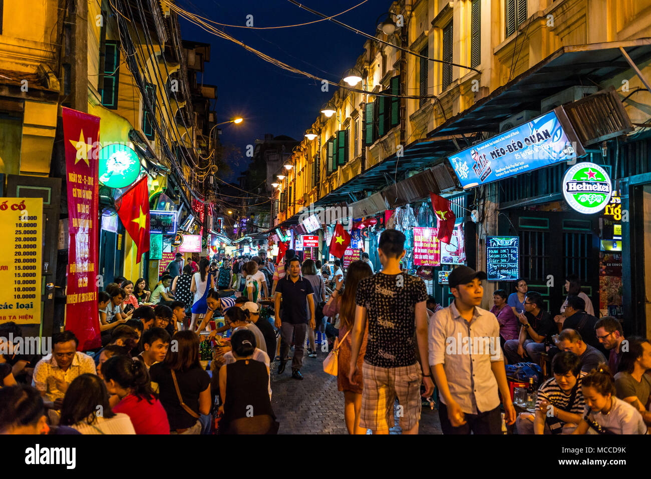 Ta Hien street, also called the Beer street, a busy crowded street full of bars and restaurants and hundreds of people sitting outside eating out enjo Stock Photo