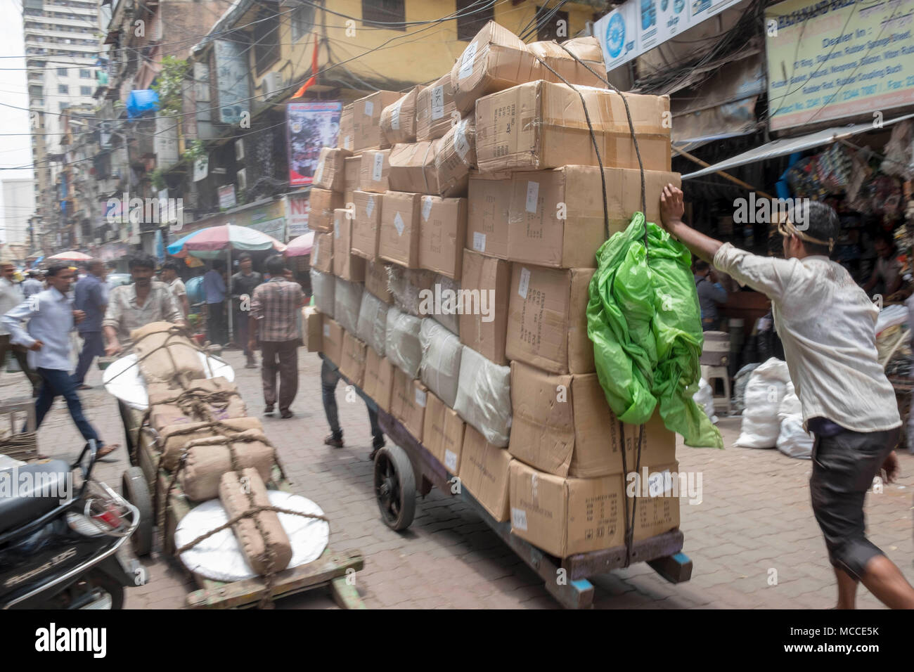 vendors pushing an over-laden cart in a street off Nagdevi street near Crawford Market in Mumbai, India - Stock Image