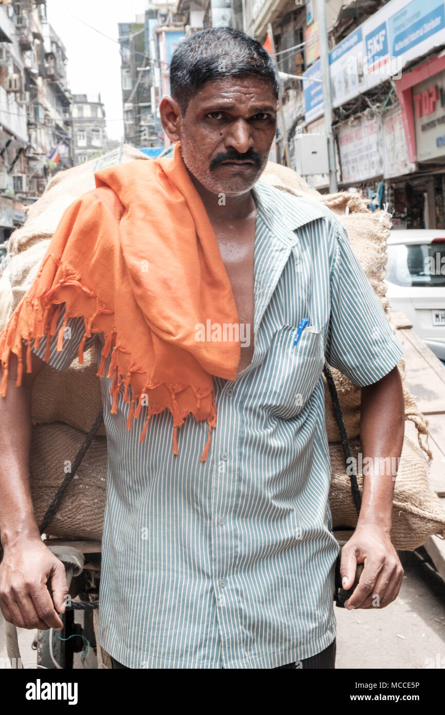 An Indian man with a moustached holding a hand cart in Nagdevi street, near Crawford market in Mumbai - Stock Image
