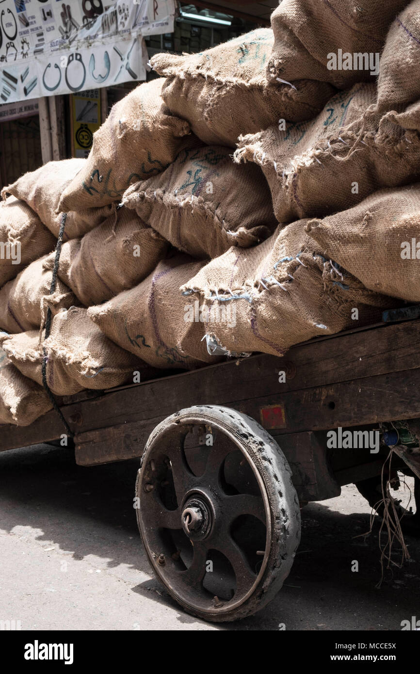 Over-laden hand cart with sacks full of charcoal on Nagdevi street near Crawford Market in Mumbai - Stock Image