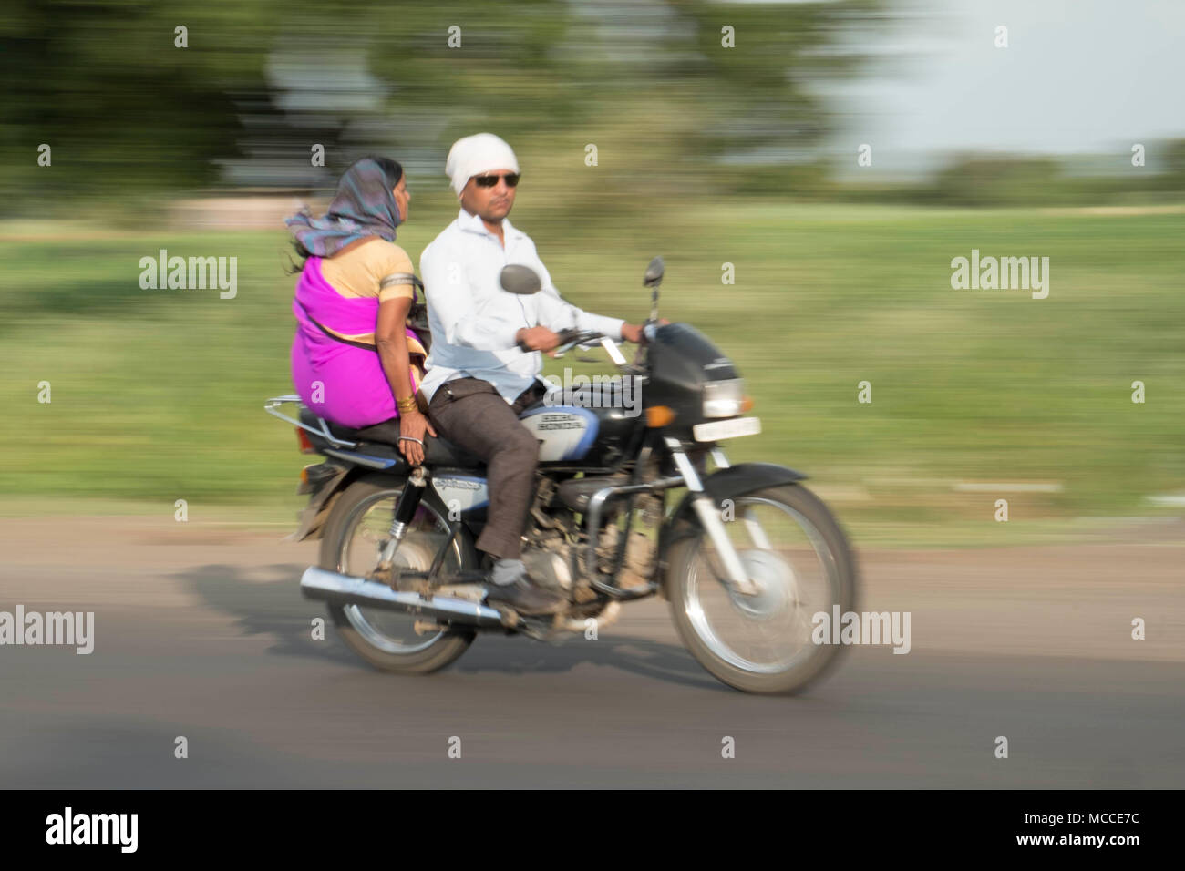 A woman in a spree sitting side saddle as a passenger on a speeding motorbike in India - Stock Image