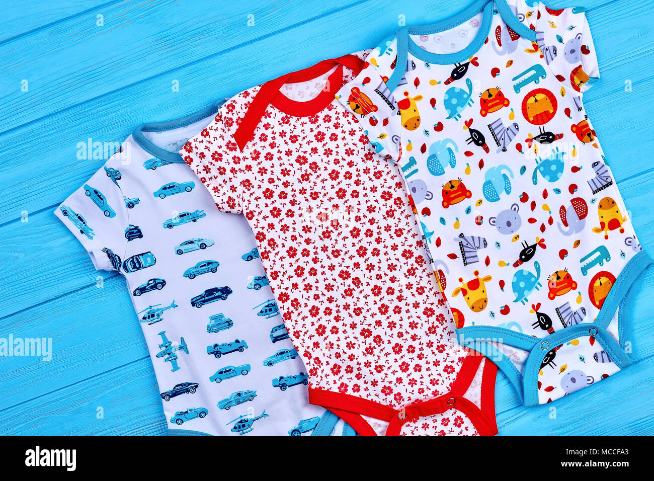 28b999c219f Natural cotton bodysuits for newborn. Set of brightful printed toddlers  rompers on blue wooden background
