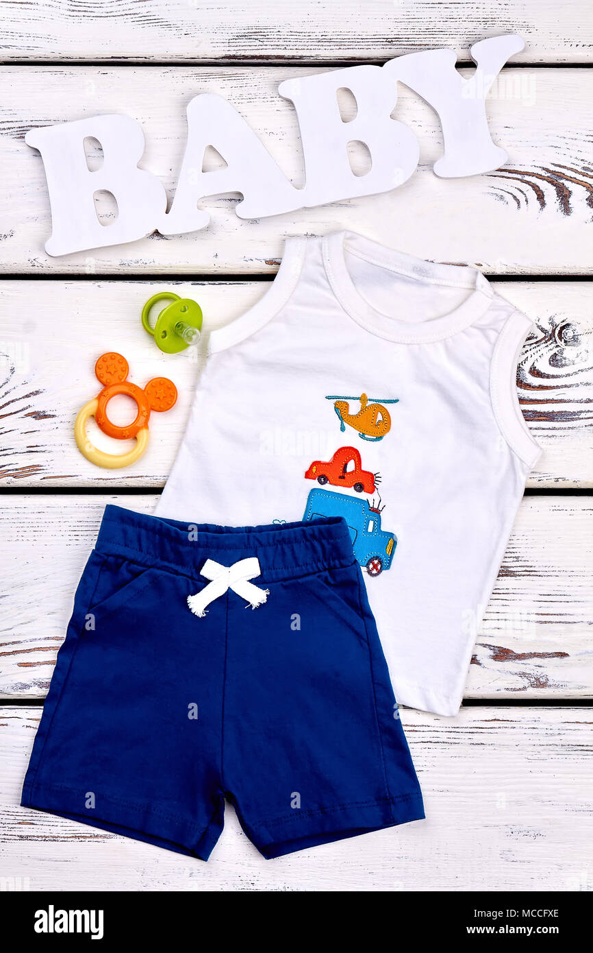 4fa228f96 Baby boy fashion boutique garment. Little boy cute brand shorts and t-shirt,  teether, pacifier, white wooden background, top view.
