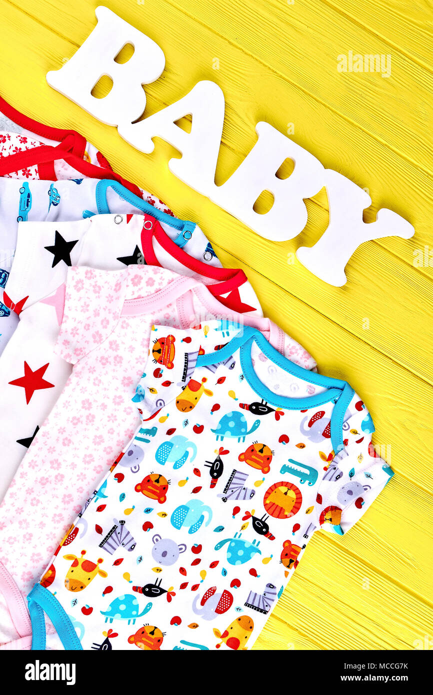 84d4a17da Newborn kids organic clothes, top view. Babies fashion collection of soft  bodysuits on yellow wooden background, word baby. Infants garment on sale.