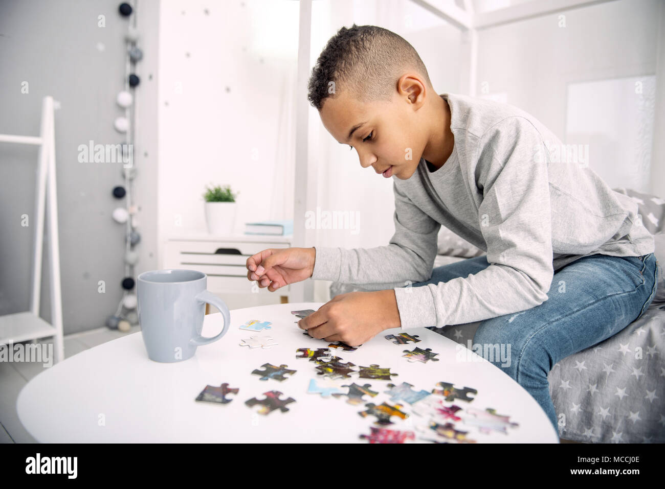 Serious nice boy assembling puzzle - Stock Image