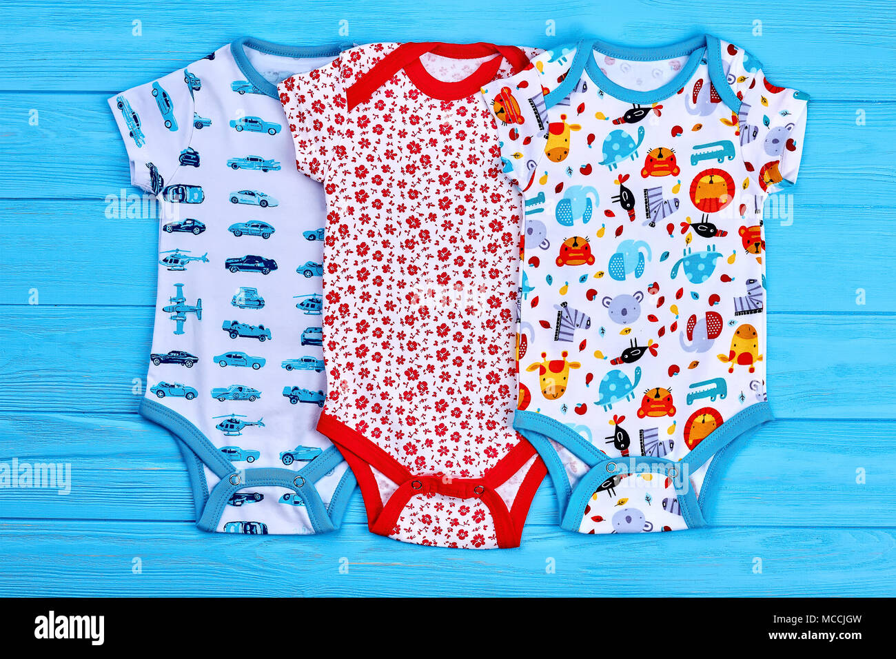 35c83b379 Set of beautiful bodysuits for newborn. Patterned cotton rompers for infant  baby, blue wooden background. Shop organic brand clothing for infant baby.