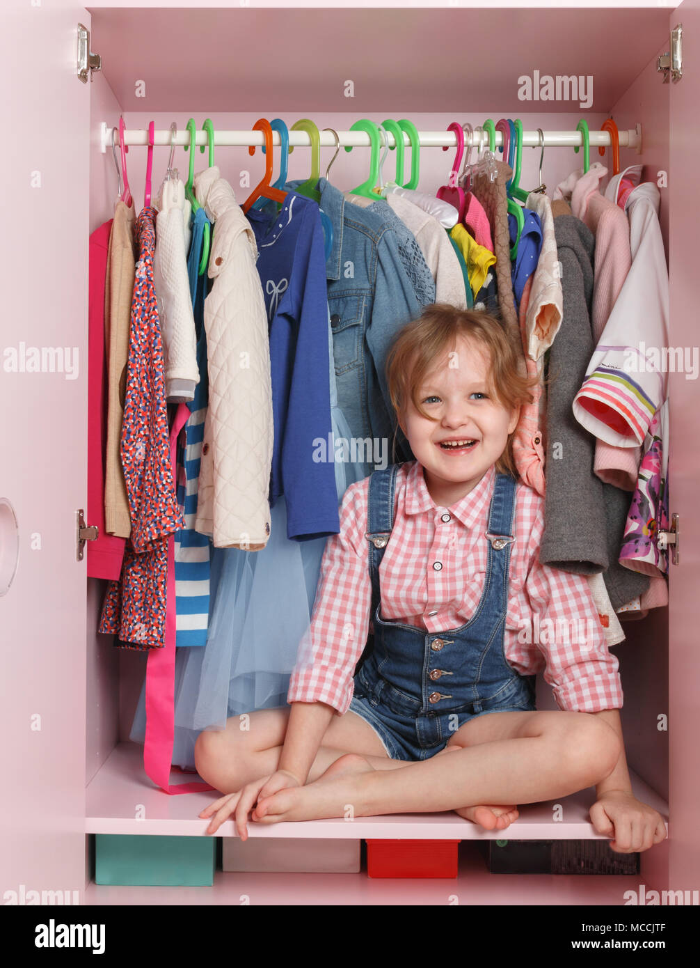 A little girl is sitting in a closet with a children's department. Storage system for children's things - Stock Image