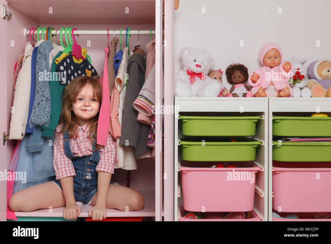 A little girl is sitting in a closet with a children's department. Storage system for children's things and toys - Stock Image