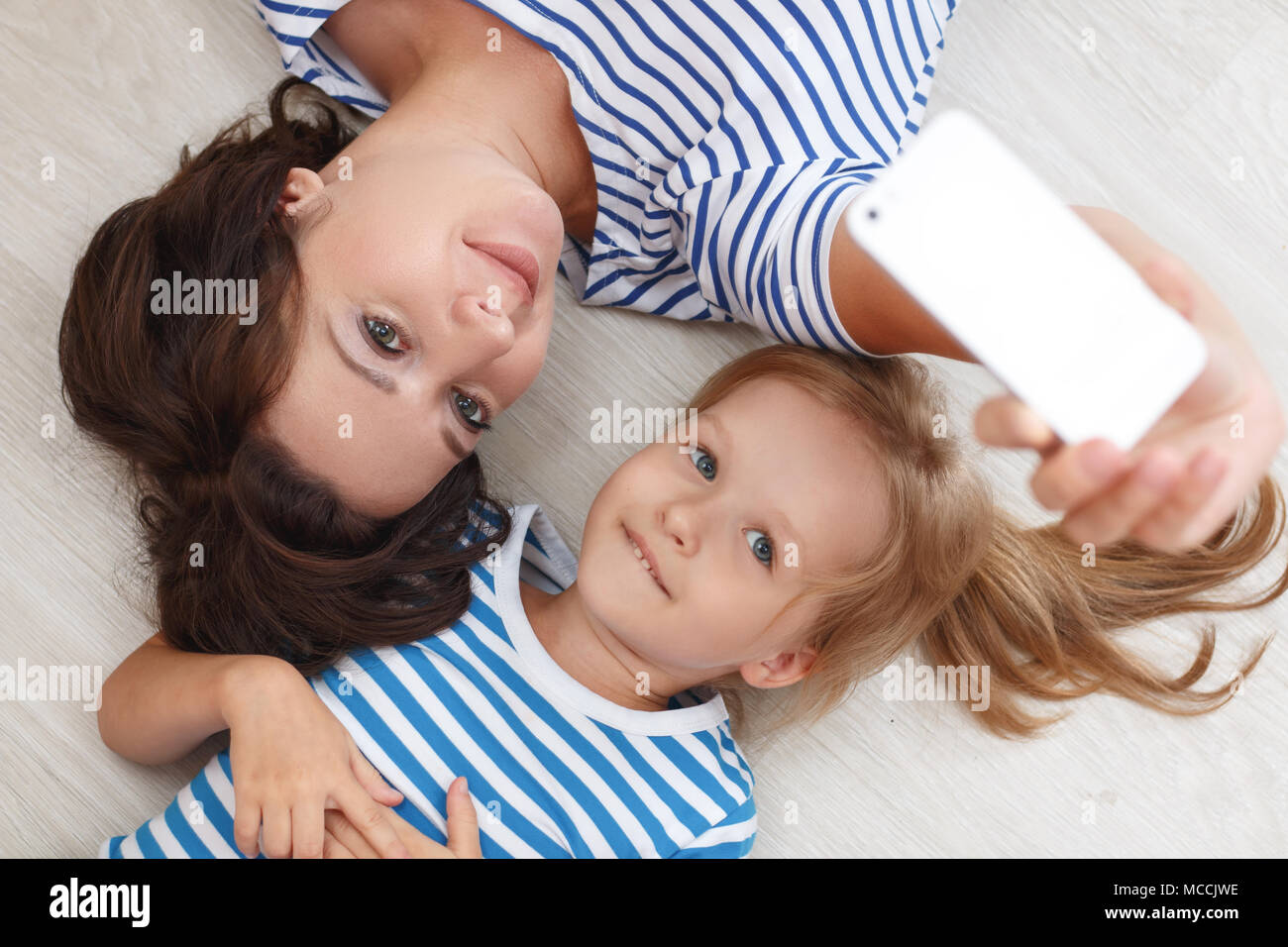 Mother and daughter making a selfie. Family holiday and togetherness, smiling and hugging, having fun. - Stock Image