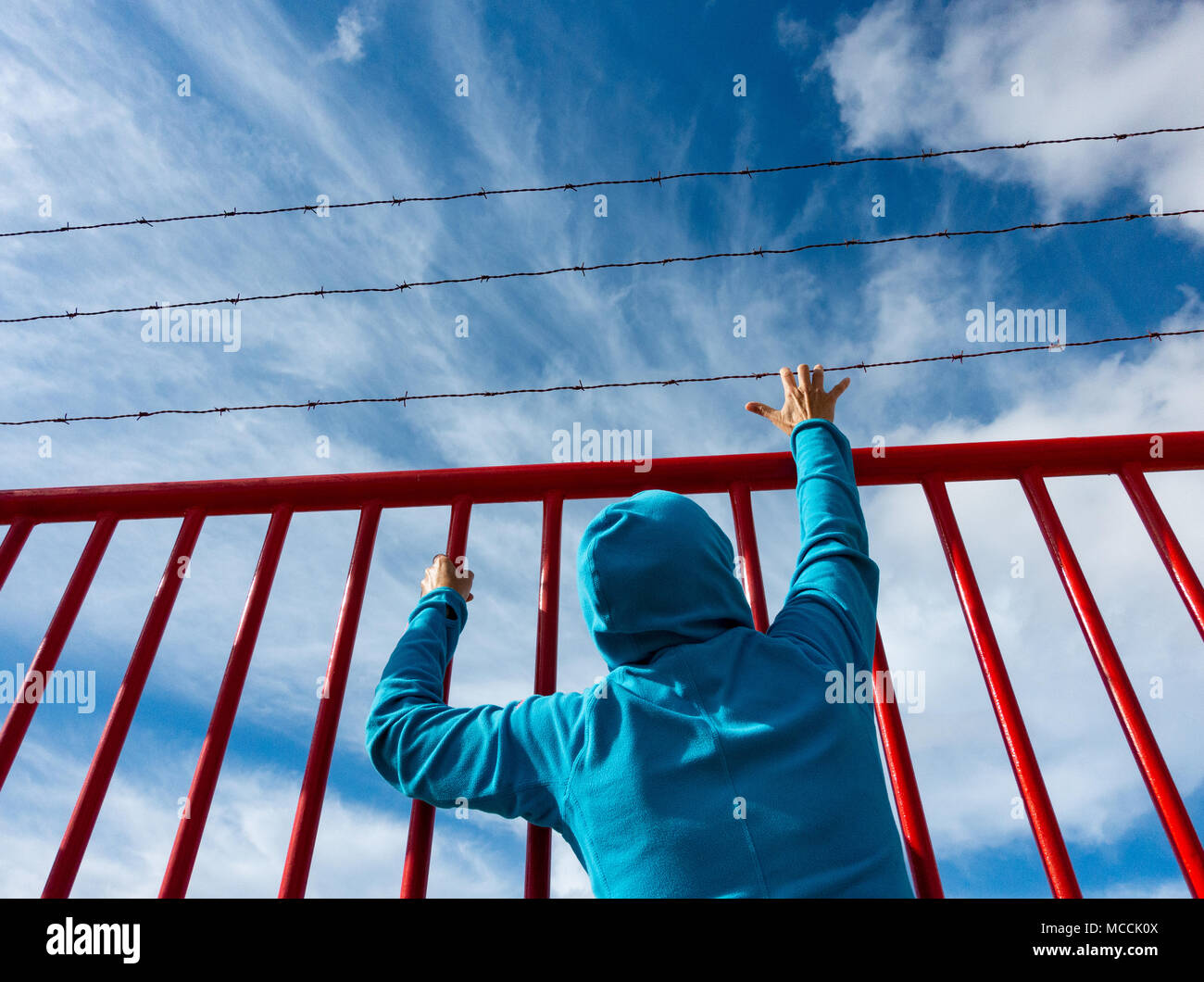 Woman behind bars topped with barbed wire: asylum,refugee,prison,detention,brexit, borders... concept image - Stock Image