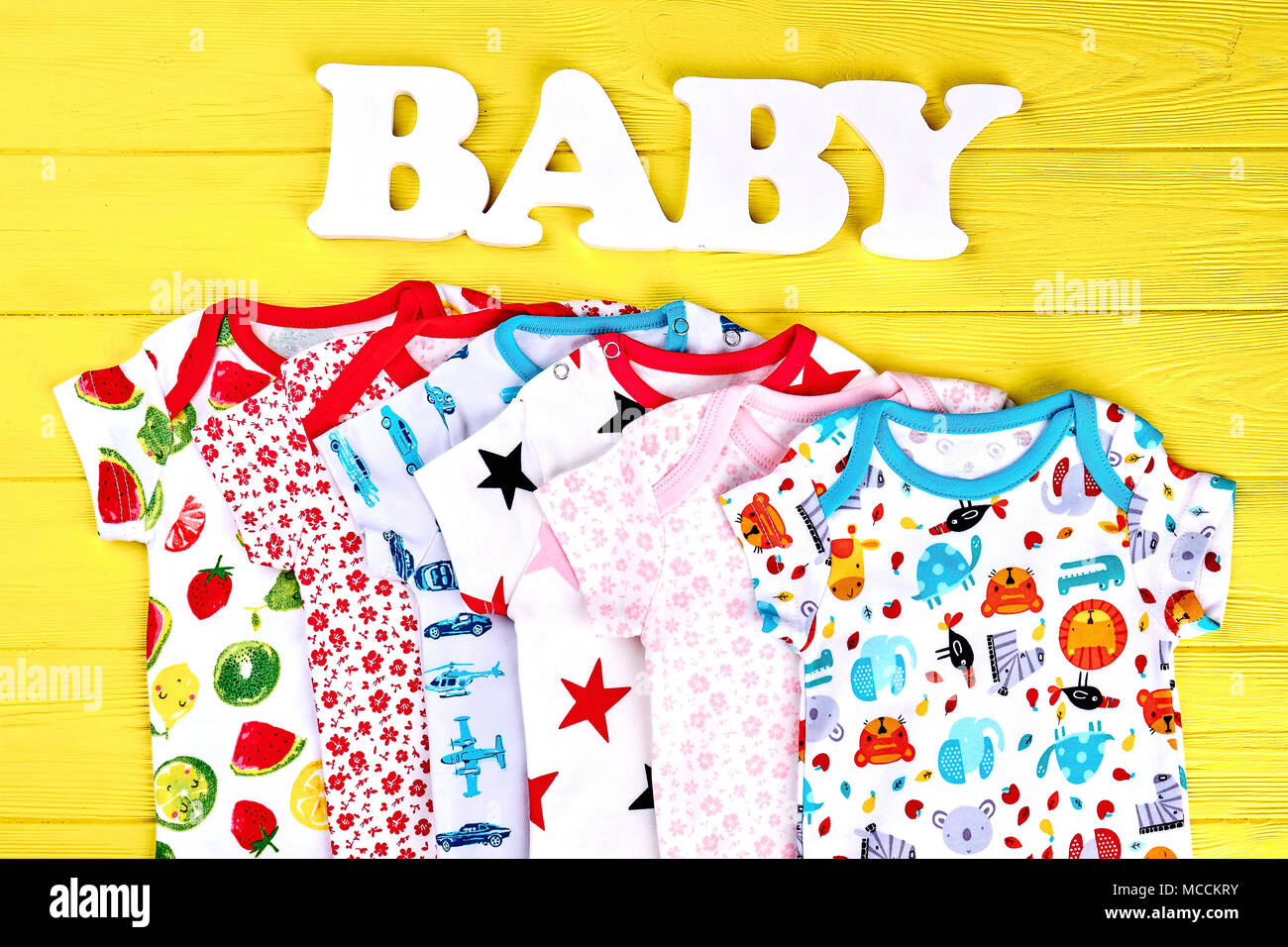 6c2a4d28a Baby soft fashion clothes background. Infants collection of rompers, word  baby on yellow wooden background.