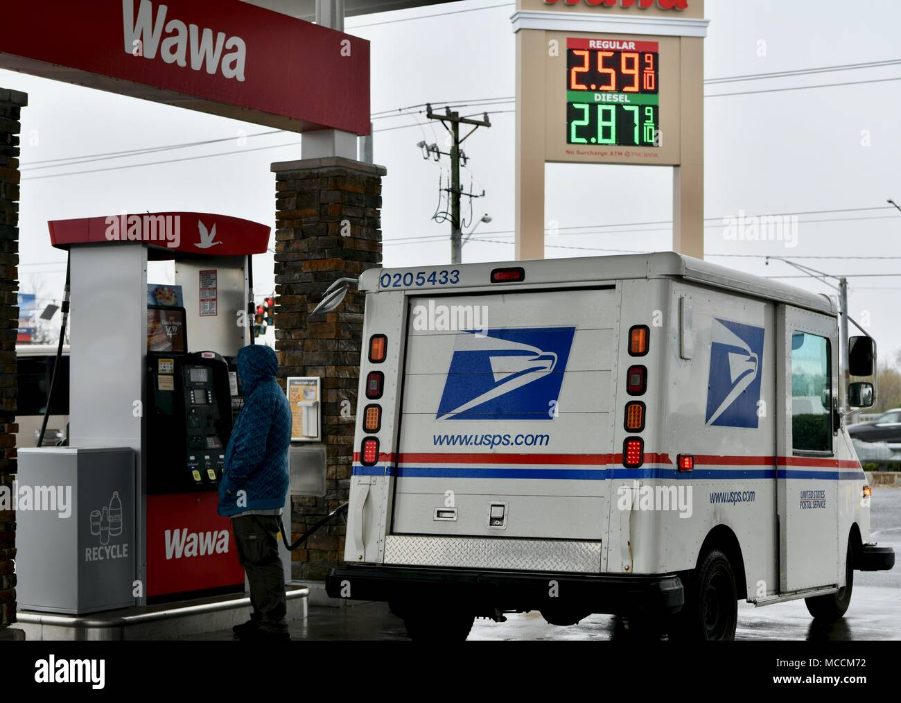 united states postal service (usps) van filling up on gasoline in delaware,  usa