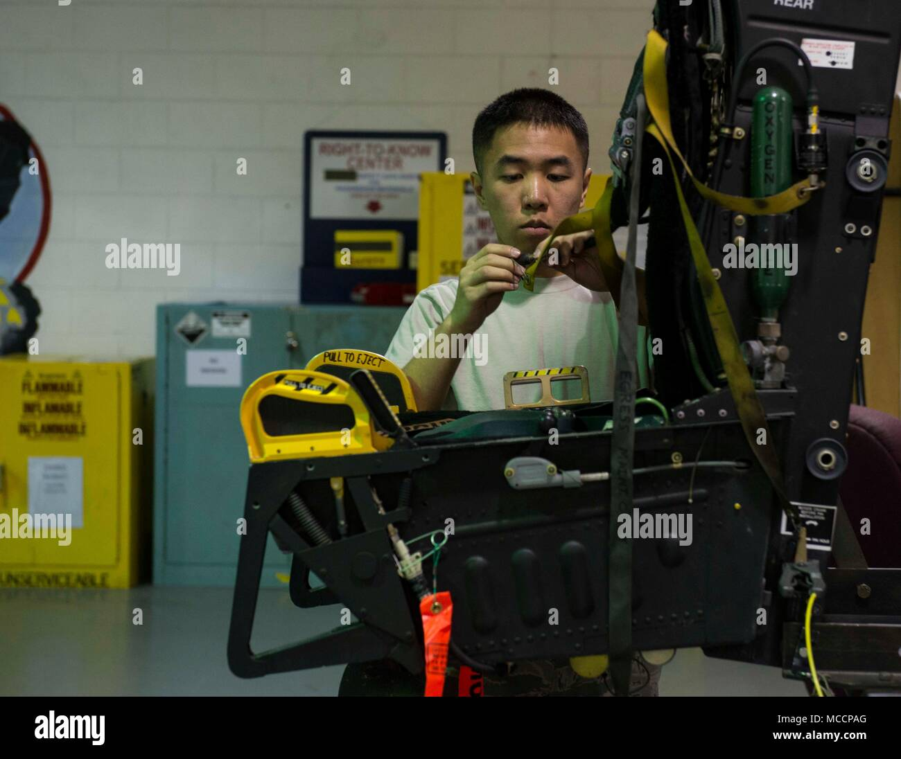Airman 1st Class Shu Hsu, 18th Component Maintenance Squadron egress systems journeyman, performs a visual inspection on an F-15 Eagle ejection seat Feb. 7, 2018, at Kadena Air Base, Japan. Hsu enjoys the specialization of his job and takes great pride in practicing excellence with his tasks. (U.S. Air Force photo by Senior Airman Jessica H. Smith) - Stock Image