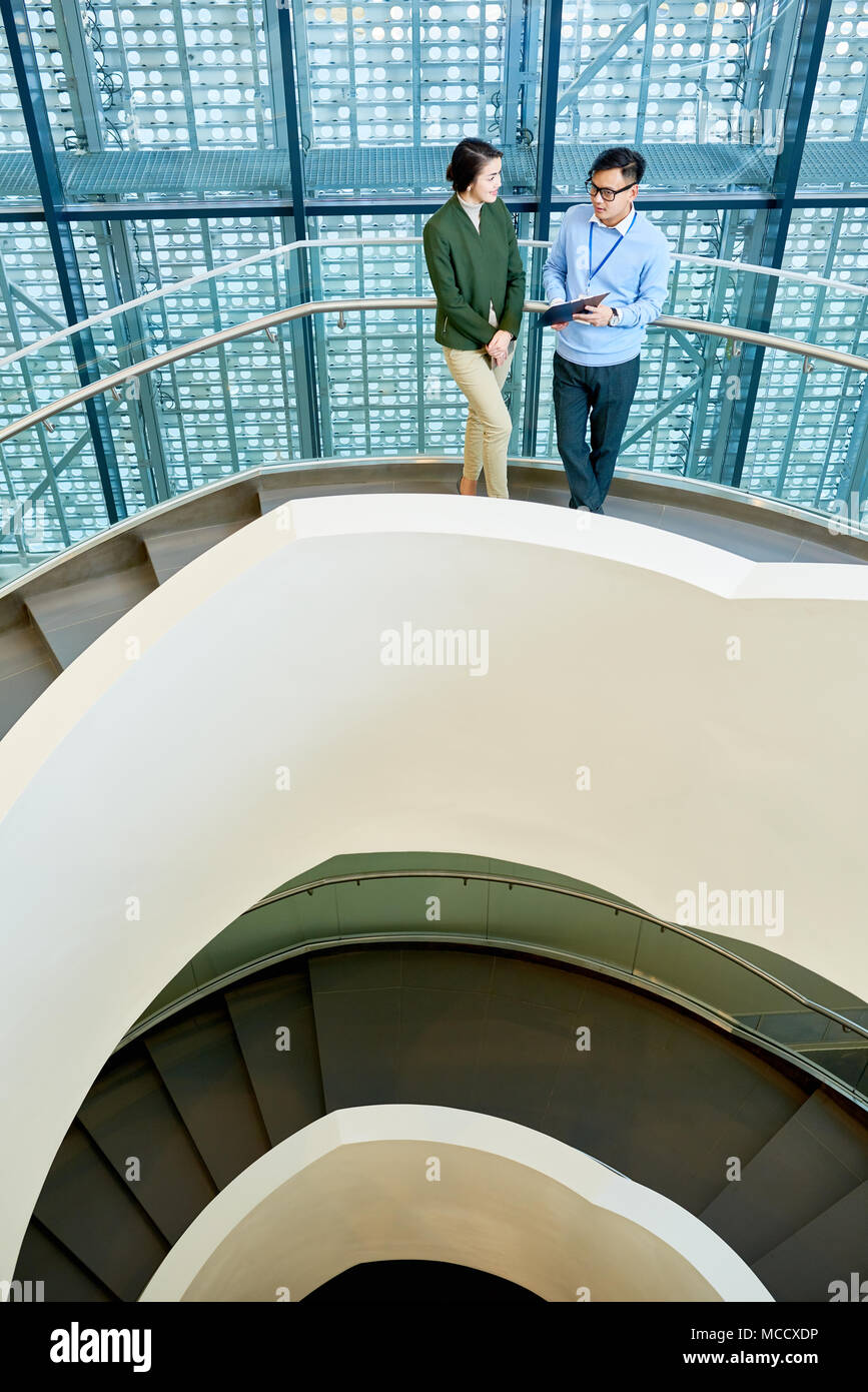 Having Discussion on Spiral Concrete Staircase - Stock Image
