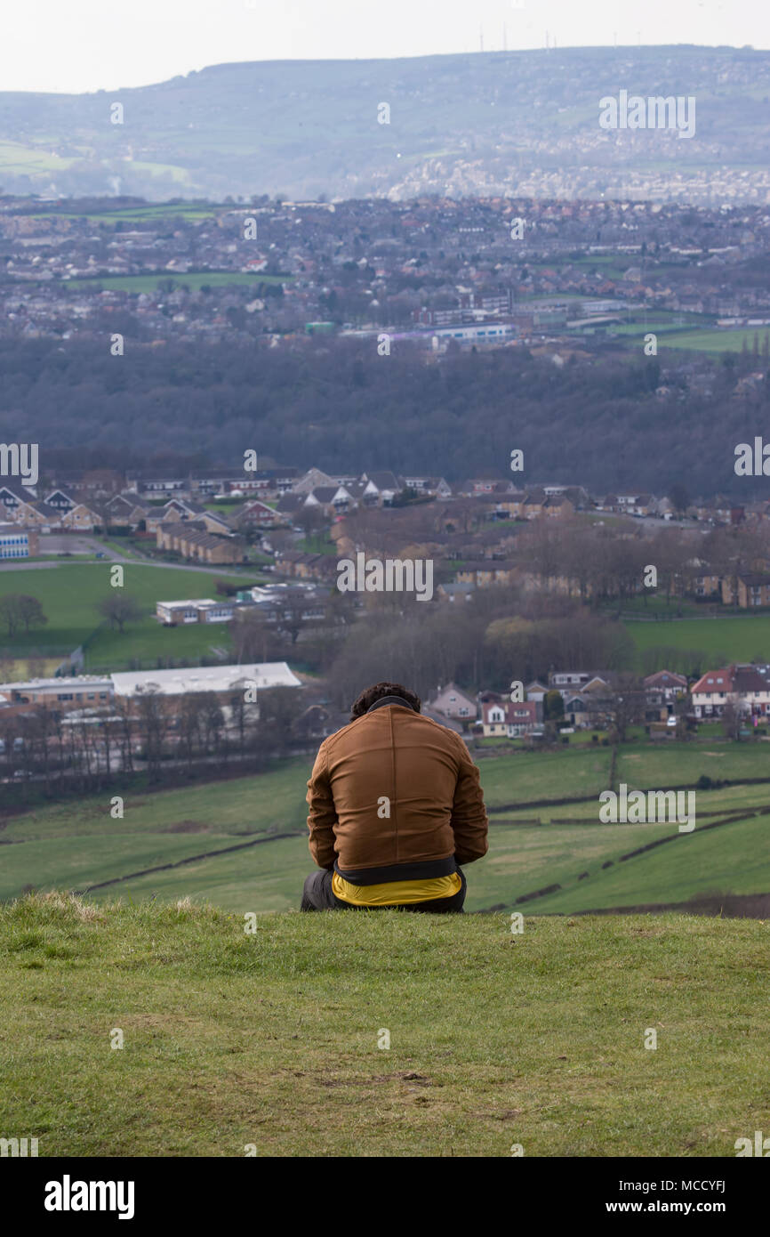 Solitary figure absorbed in texting with a panoramic view of West Yorkshire before him - Stock Image