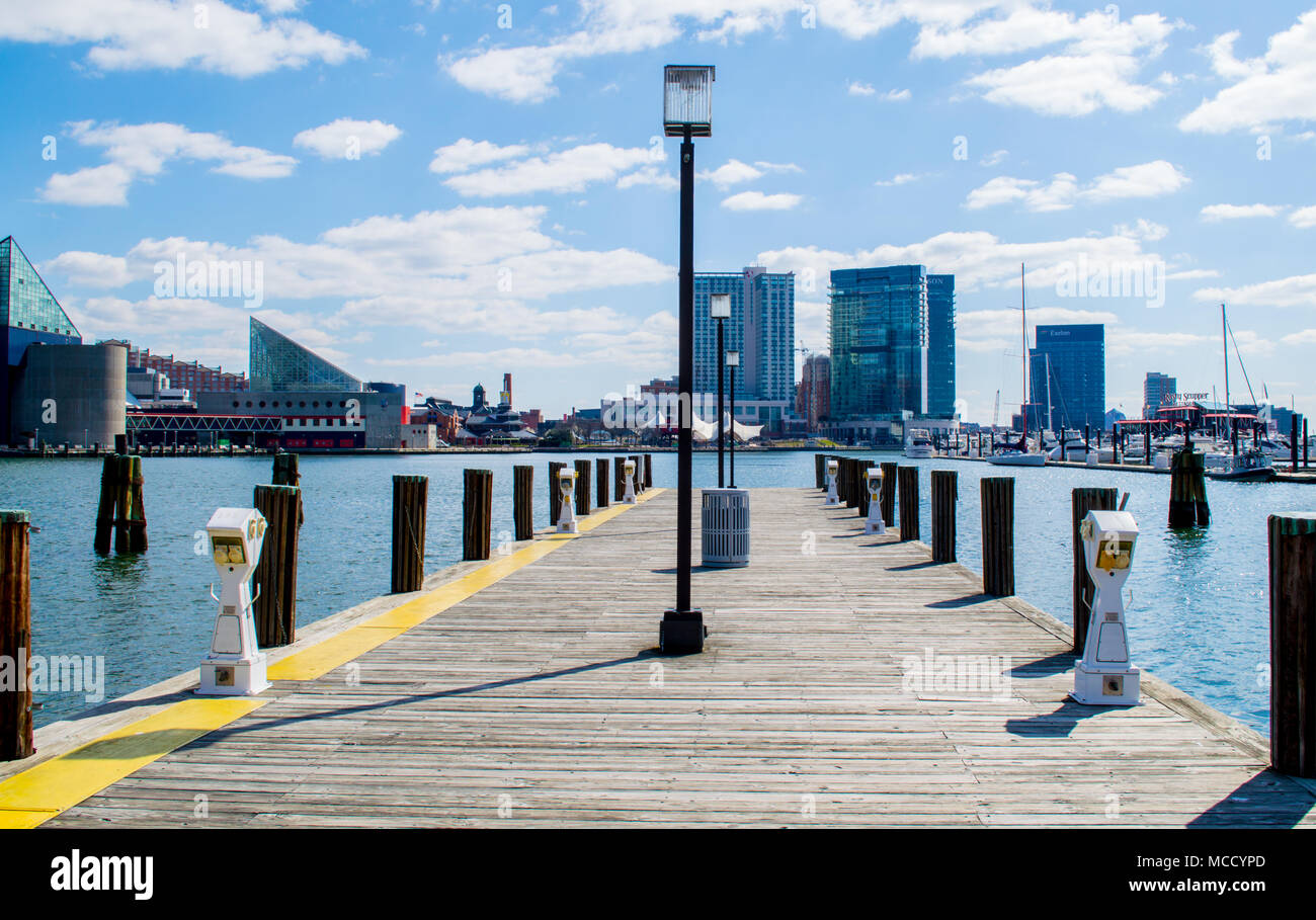 view of Baltimore's Inner Harbor from a weathered wooden pier on a sunny spring day - Stock Image