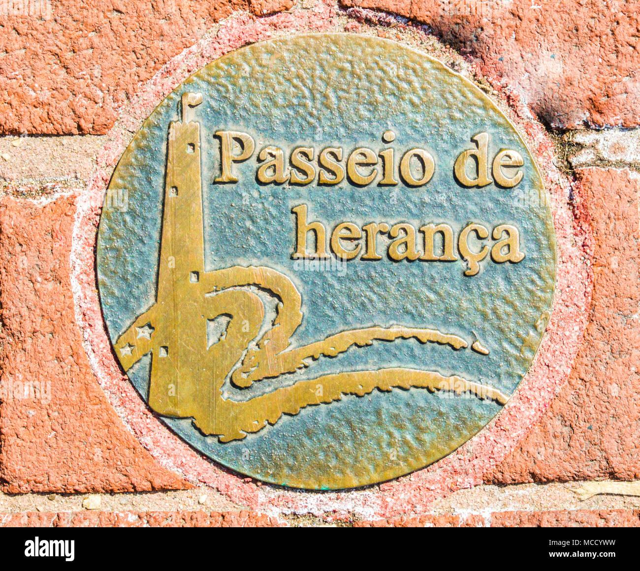 decorative metal sidewalk disc in Spanish language along Baltimore's Heritage Walk historical walking trail - Stock Image
