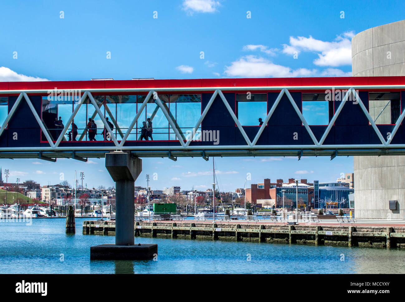 people strolling along the modern enclosed glass walkway going over Baltimore's Inner Harbor at the National Aquarium - Stock Image