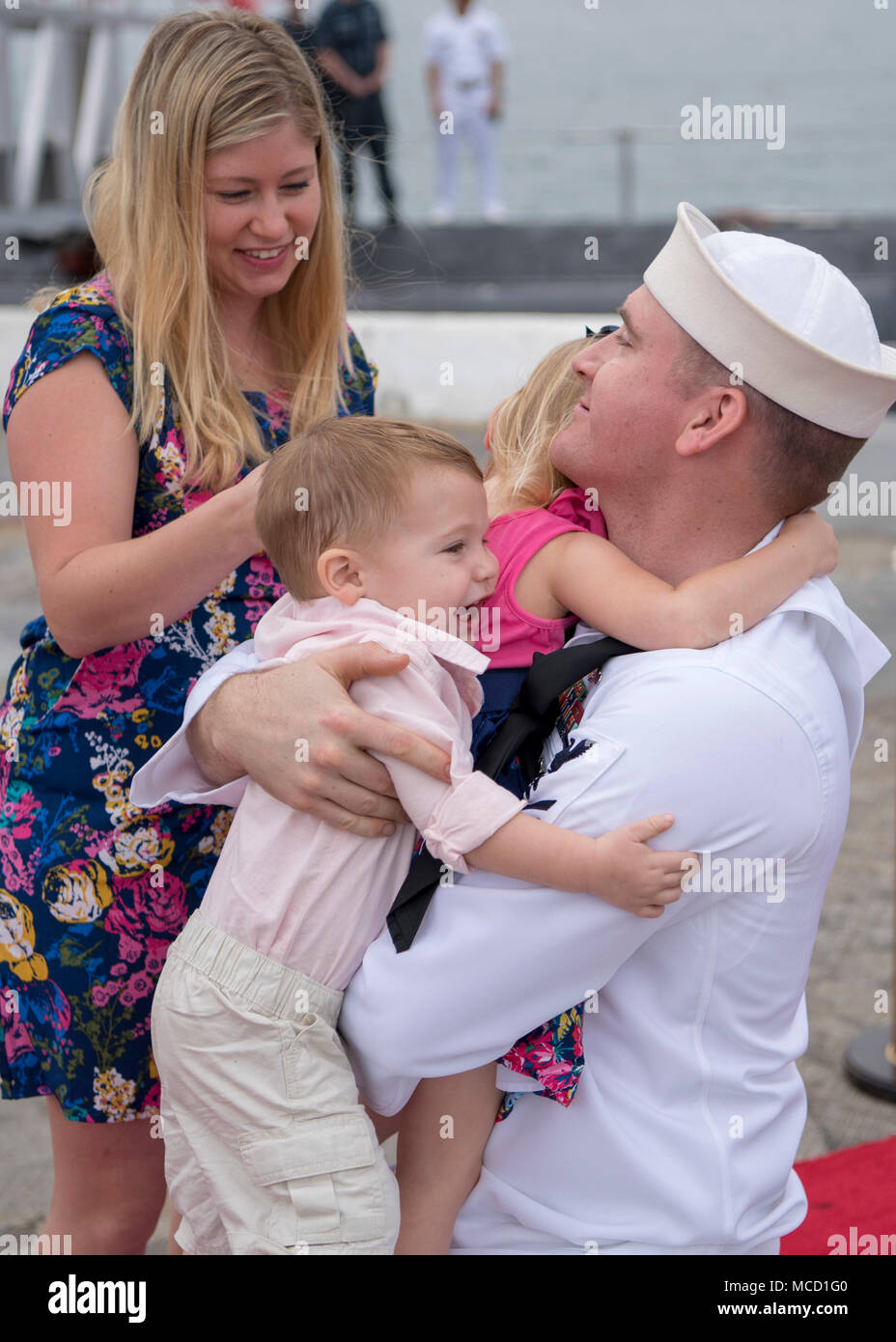 180214-N-LY160-0159 PEARL HARBOR, Hawaii (February 14, 2018) Machinist's Mate (Nuclear) 1st Class Thomas Bolin, assigned to the Virginia-class fast-attack submarine USS Texas (SSN 775) and native of Abilene, Texas, hugs his family on the submarine pier in Joint Base Pearl Harbor-Hickam, Feb. 14. USS Texas successfully completed a Western Pacific deployment in support of national security. (U.S. Navy photo by Mass Communication Specialist 2nd Class Michael H. Lee/ Released) - Stock Image