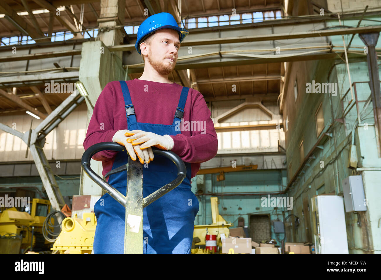 Young Factory Worker at Spacious Warehouse - Stock Image