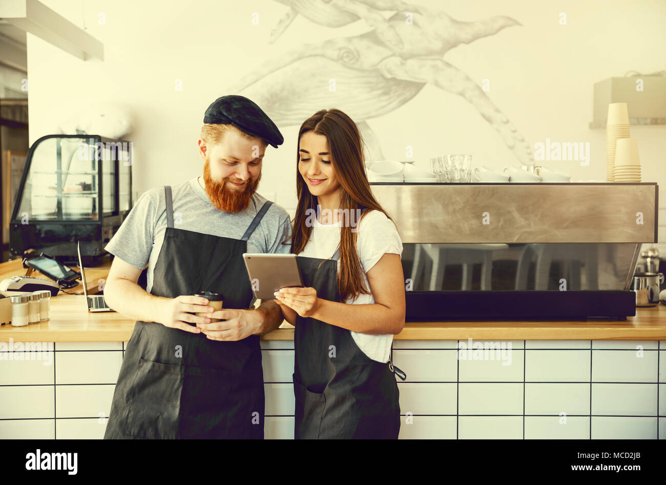 Coffee Business Concept - Positive young bearded man and beautiful attractive lady barista couple in apron. - Stock Image
