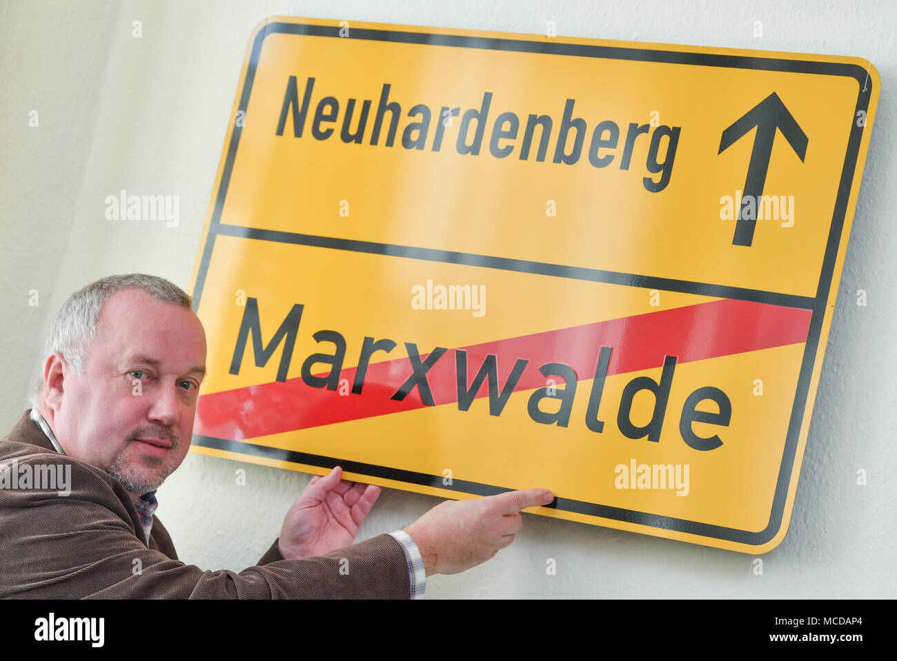 10 April 2018, Germany, Neuhardenberg: Dietmar Zimmermann, chairman of the local heritage association 'Heimatverein Neuhardenberg e.V.' places a road sign which reads 'Neuhardenberg - Marxwalde' on a wall of the local heritage museum. The town was previoulsy known as Marxwalde after German philosopher, economist and social theorist Karl Marx (May, 05 1818 - March, 14 1883) during the GDR era and renamed to Neuhardenberg after the fall of the Berlin Wall. Photo: Patrick Pleul/dpa-Zentralbild/dpa Stock Photo