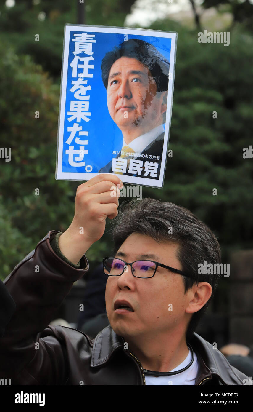 Tokyo, Japan. 14th Apr, 2018. A man holds a placard to protest against Abe cabinet at a rally in front of the National Diet in Tokyo on Saturday, April 14, 2018. Tens of thousands people gathered to demand resignation of Prime Minister Shinzo Abe for the Moritomo and Kake scandals. Credit: Yoshio Tsunoda/AFLO/Alamy Live News - Stock Image