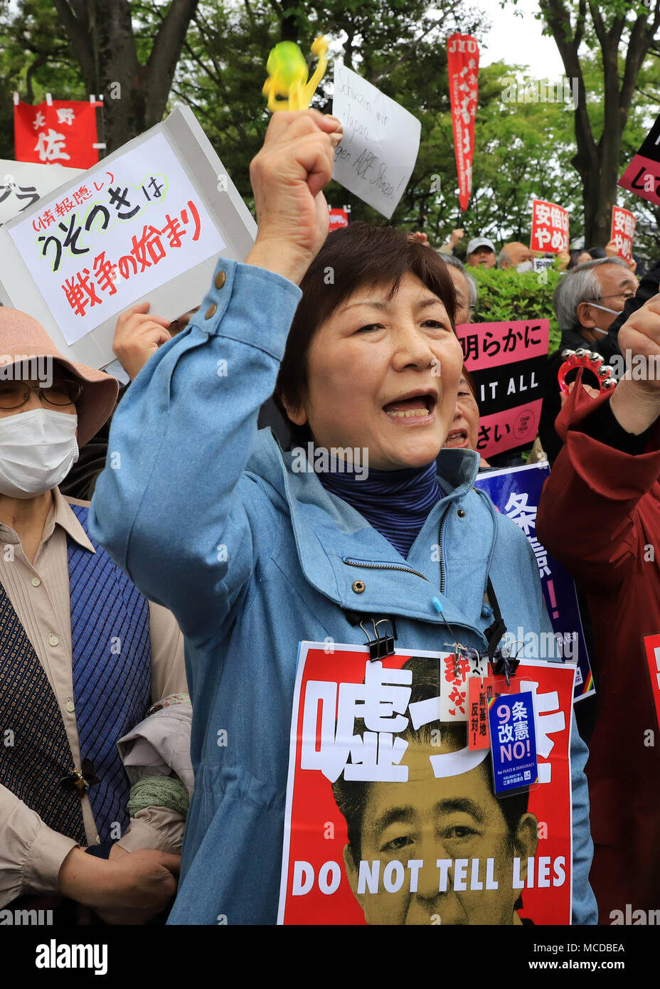 Tokyo, Japan. 14th Apr, 2018. Protestors hold placards to protest against Abe cabinet at a rally in front of the National Diet in Tokyo on Saturday, April 14, 2018. Tens of thousands people gathered to demand resignation of Prime Minister Shinzo Abe for the Moritomo and Kake scandals. Credit: Yoshio Tsunoda/AFLO/Alamy Live News - Stock Image