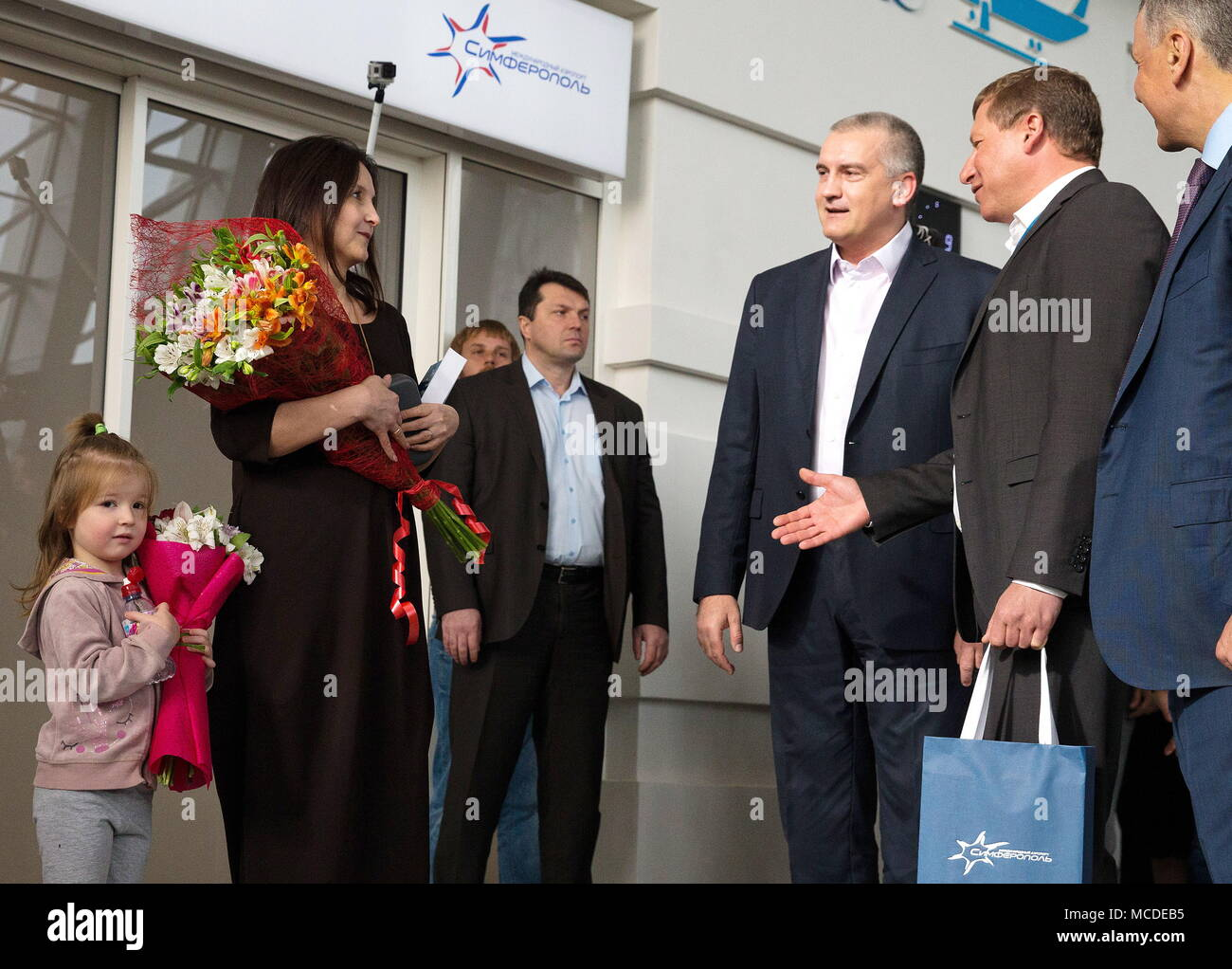 SIMFEROPOL, RUSSIA - APRIL 16, 2018: The Head of Russia's Republic of Crimea, Sergei Aksyonov (3rd R), the General Director of the Simferopol International Airport, Yevgeny Plaksin (2nd R), and the Chairman of the State Council of the Republic of Crimea, Vladimir Konstantinov (R), welcome Svetlana Kovrizhina with daughter Agata from Ufa (L), the first travellers to arrive at the new passenger terminal building at the Simferopol Airport in Simferopol, Crimea, Russia. Sergei Malgavko/TASS - Stock Image