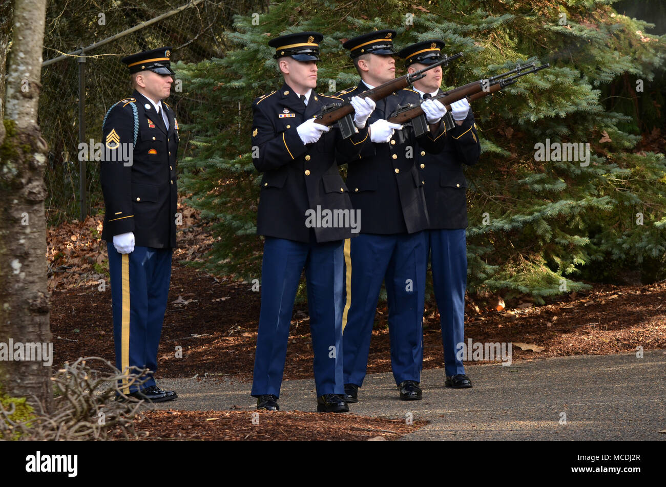 A firing party team of Oregon Army National Guard Soldiers consisting of SPC Michael Banks, SGT Everett Mayers and SPC Isaac Yocum (left to right), listen to commands given by Staff Sgt. Joshua Flores (far left) while supporting a Navy funeral at Willamette National Cemetery, Portland, Ore., Feb. 7, 2018.  (U.S. Air National Guard photo by Master Sgt. John Hughel, 142nd Fighter Wing Public Affairs) - Stock Image