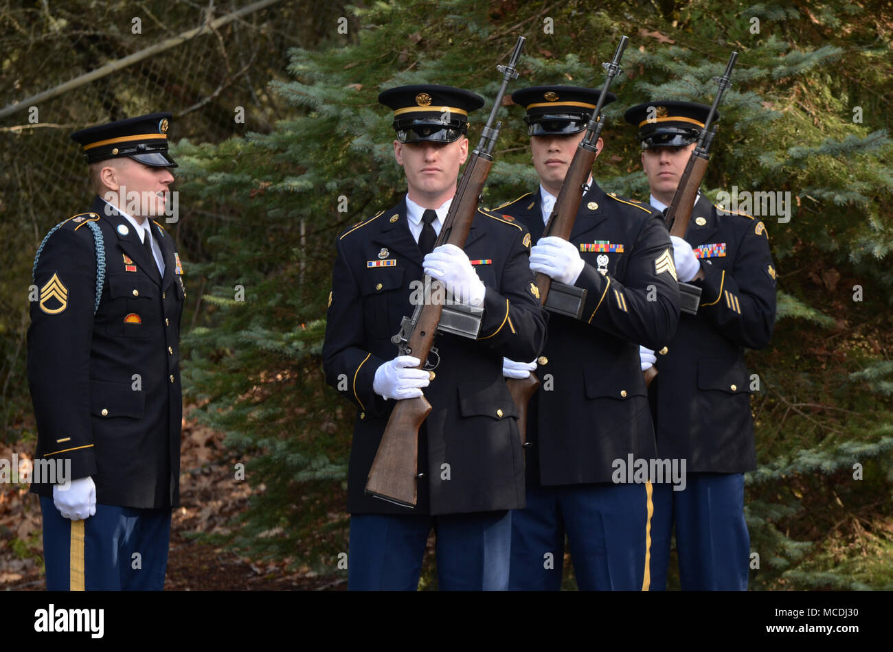 A firing party team of Oregon Army National Guard Soldiers consisting of SPC Michael Banks, SGT Everett Mayers and SPC Isaac Yocum (left to right), listen to commands given by SSGT Joshua Flores (far left) while supporting a Navy funeral at Willamette National Cemetery, Portland, Ore., Feb. 7, 2018.  (U.S. Air National Guard photo by Master Sgt. John Hughel, 142nd Fighter Wing Public Affairs) - Stock Image