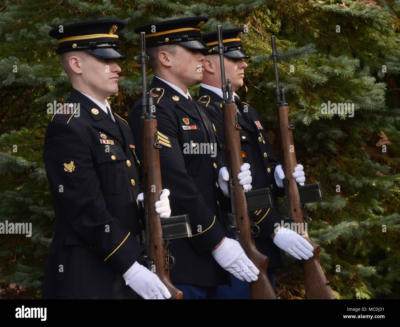 A firing party team of Oregon Army National Guard Soldiers consisting of Specialist Michael Banks, Sergeant Everett Mayers and Specialist Isaac Yocum (left to right), present a full rifle salute while supporting a Navy funeral at Willamette National Cemetery, Portland, Ore., Feb. 7, 2018.  (U.S. Air National Guard photo by Master Sgt. John Hughel, 142nd Fighter Wing Public Affairs) - Stock Image