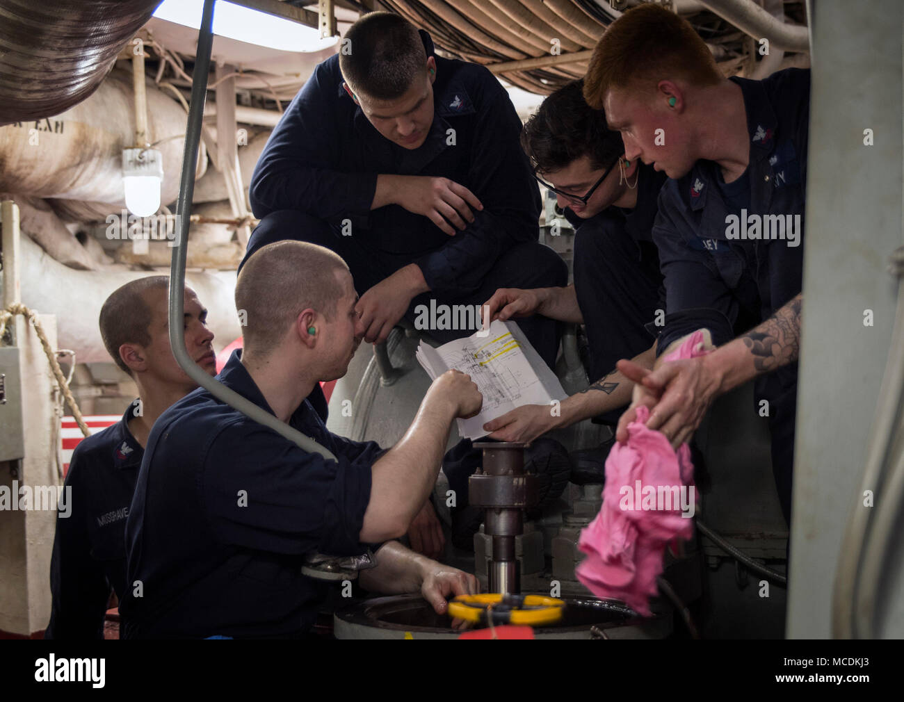 180214-N-WF272-156 GULF OF THAILAND (Feb. 14, 2018) Engineering department Sailors verify schematics during a rebuild of a lube oil service pump in the forward main machinery room of the amphibious assault ship USS Bonhomme Richard (LHD 6). Bonhomme Richard is operating in the Indo-Asia-Pacific region as part of a regularly scheduled patrol and provides a rapid-response capability in the event of a regional contingency or natural disaster. (U.S. Navy photo by Mass Communication Specialist 2nd Class Diana Quinlan/Released) - Stock Image