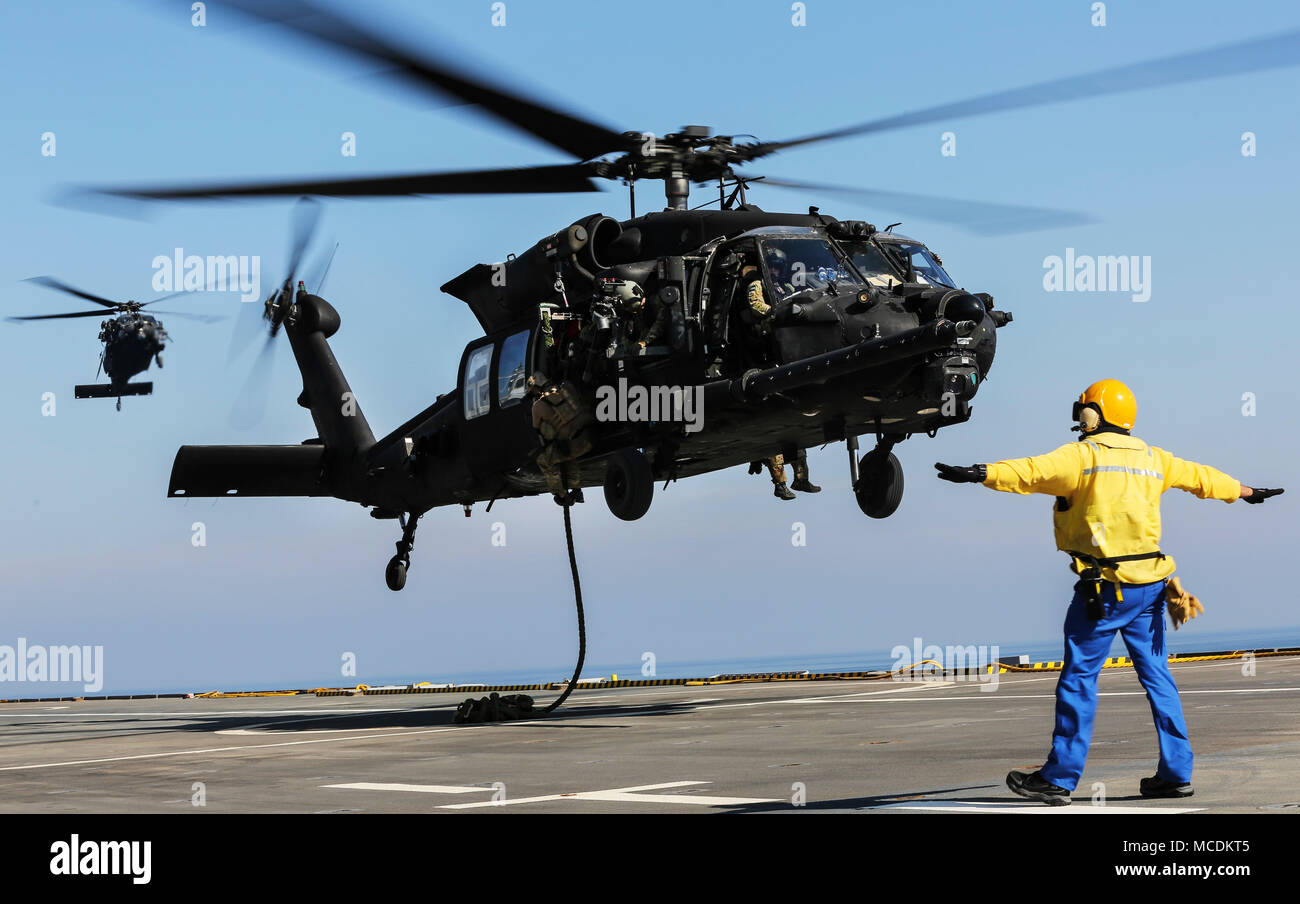 U.S. 5TH FLEET AREA OF OPERATIONS (Feb. 6, 2018) U.S. military forces fast rope out of an U.S. Army MH-60 Black Hawk onto the deck of French amphibious assault ship LHD Tonnerre (L9014) during a bilateral training evolution.  The Tonnerre, with embarked Marines and Sailors from Naval Amphibious Force, Task Force 51/5th Marine Expeditionary Brigade and US Special Operations Forces are conducting maritime security operations within the U.S. 5th Fleet area of operations to ensure regional stability, freedom of navigation and the free flow of commerce with regional partners. (U.S. Marine Corps pho - Stock Image