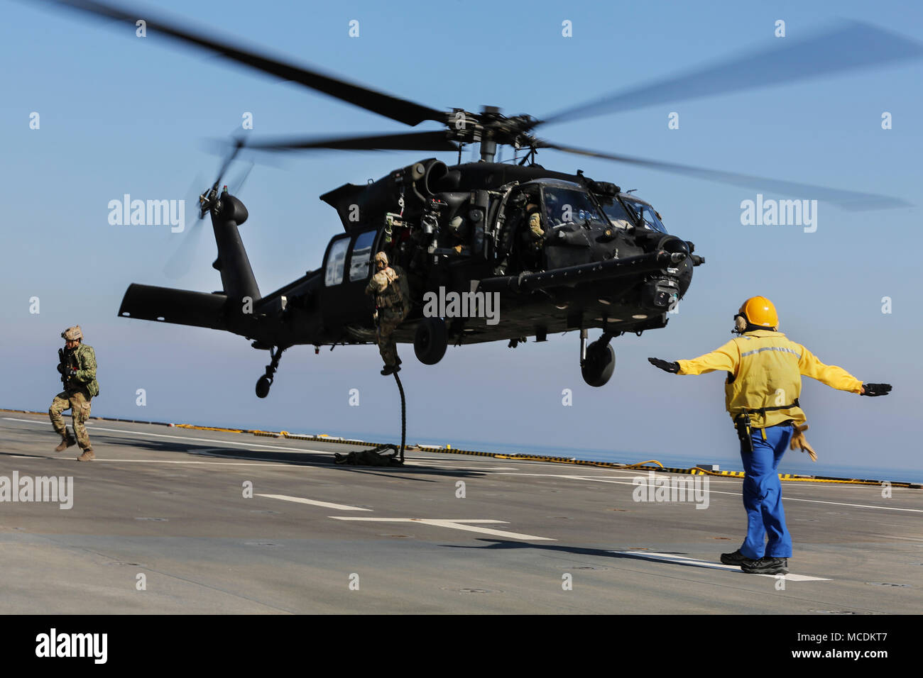 U.S. 5TH FLEET AREA OF OPERATIONS (Feb. 6, 2018) U.S. military forces fast rope out of an U.S. Army MH-60 Black Hawk onto the deck of French amphibious assault ship LHD Tonnerre (L9014) during a bilateral training evolution. The Tonnerre, with embarked Marines and Sailors from Naval Amphibious Force, Task Force 51/5th Marine Expeditionary Brigade and US Special Operations Forces are conducting maritime security operations within the U.S. 5th Fleet area of operations to ensure regional stability, freedom of navigation and the free flow of commerce with regional partners. (U.S. Marine Corps phot - Stock Image