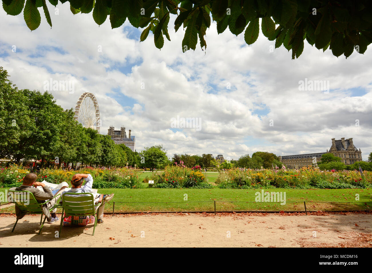 A couple reading the newspaper at the Tuellieries gardens of the Louvre in Paris. - Stock Image