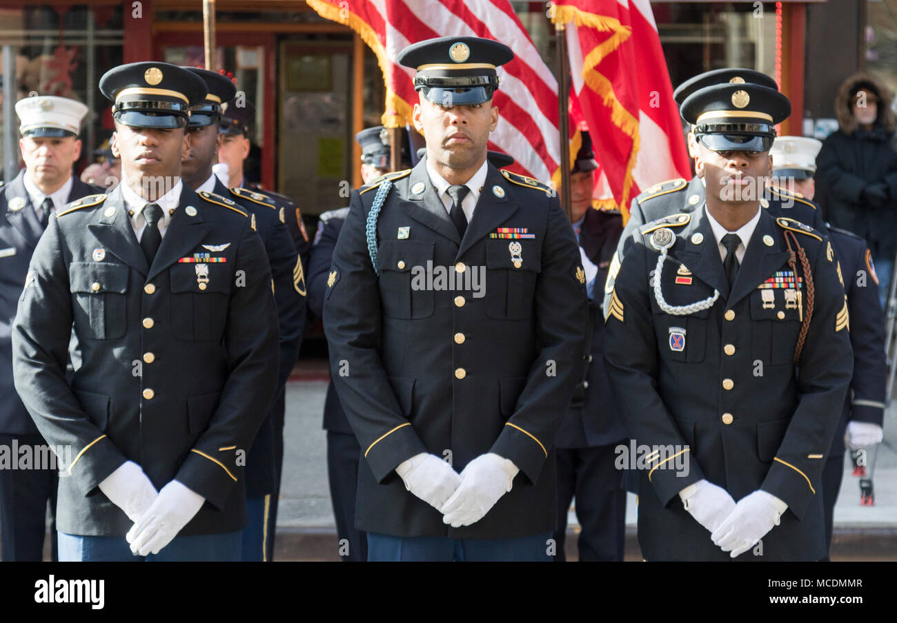 Honor Guard Soldiers with the N.Y. Army National Guard stand ready for the funeral procession to begin for Pfc. Emmanuel Mensah at Our Lady of Mount Carmel Church, Bronx, N.Y., Feb. 17, 2018. New York City fire officials credit Mensah with saving four lives during an apartment building fire Dec. 28, 2017, rescuing people three times before he returned to the building and did not come out. Pfc. Mensah completed Advanced Individual Training at Fort Lee, Va., in early Dec. 2017, and intended to serve as a wheeled vehicle mechanic and begin drilling with the New York Army National Guard's 107th Mi Stock Photo