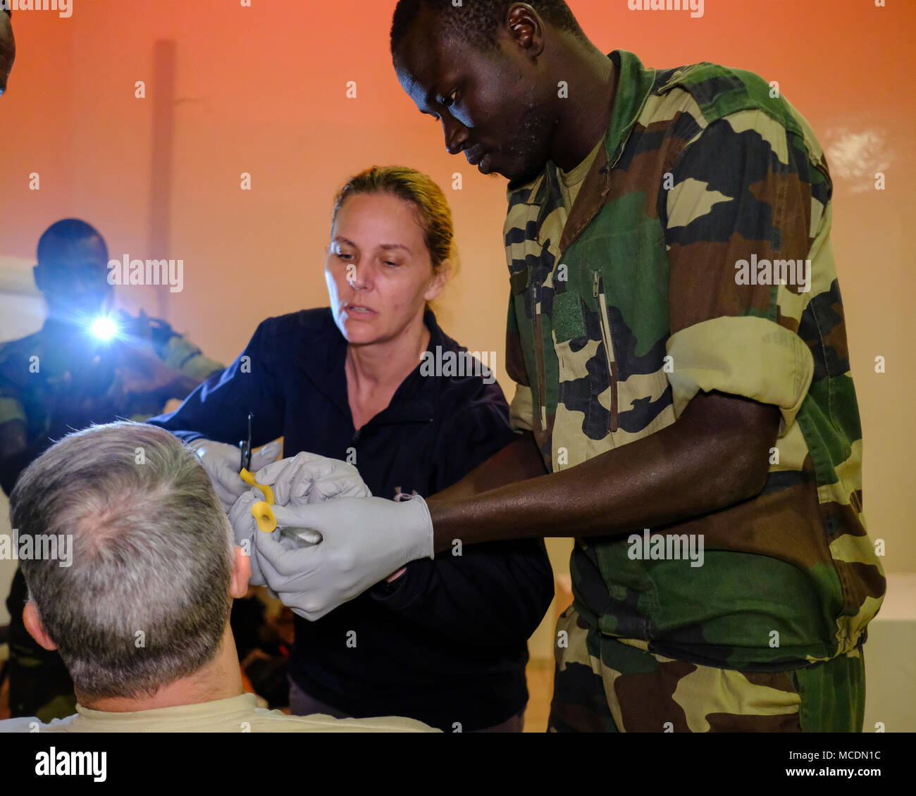 Cpl. Boubacar Seydi, infirmier with the Senegalese army, measures a nasopharyngeal airway as U.S Army Sgt. April Swafford, medic with Munson Army Health Center, Fort Leavenworth, Kansas, cuts it to proper length during a pre-hospital trauma care workshop taught by U.S. Army medical personnel at Base Militaire Bel Air, Senegal, during MEDRETE 18-1, Feb. 20, 2018. MEDRETE is a combined effort between the Senegalese government, U.S. Army Africa, and the Vermont National Guard. MEDRETE 18-1 is the first in a series of medical readiness training exercises that U.S. Army Africa is scheduled to facil - Stock Image