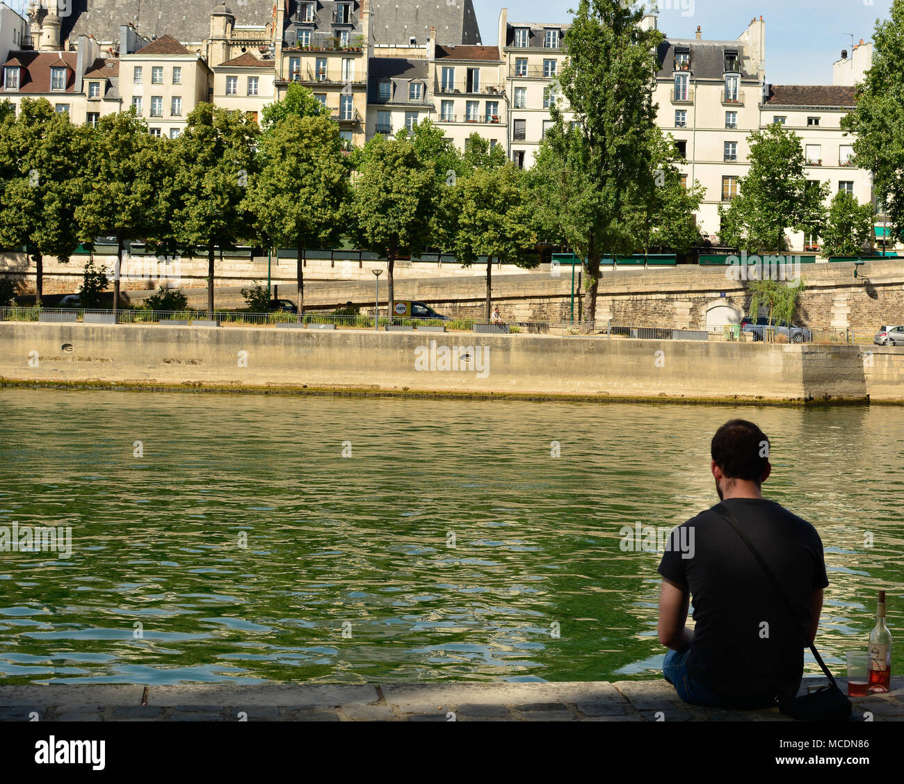 A man sits alone with a bottle of wine, relaxing on the banks of the river Seine in Paris - Stock Image