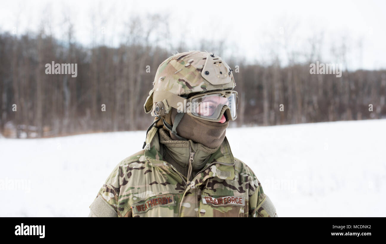 Staff Sgt. Nicole Weatherby, 91st Security Support Squadron response force member, kneels before Airmen signal a 54th Helicopter Squadron UH-1N Iroquois during a winter survival field training exercise in Turtle Mountain State Forest, N.D., Feb. 14, 2018. During the FTX, defenders vectored two 54th Helicopter Squadron UH-1N Iroquois to the landing zone and performed a simulated medical evacuation. (U.S. Air Force photo by Airman 1st Class Alyssa M. Akers) - Stock Image