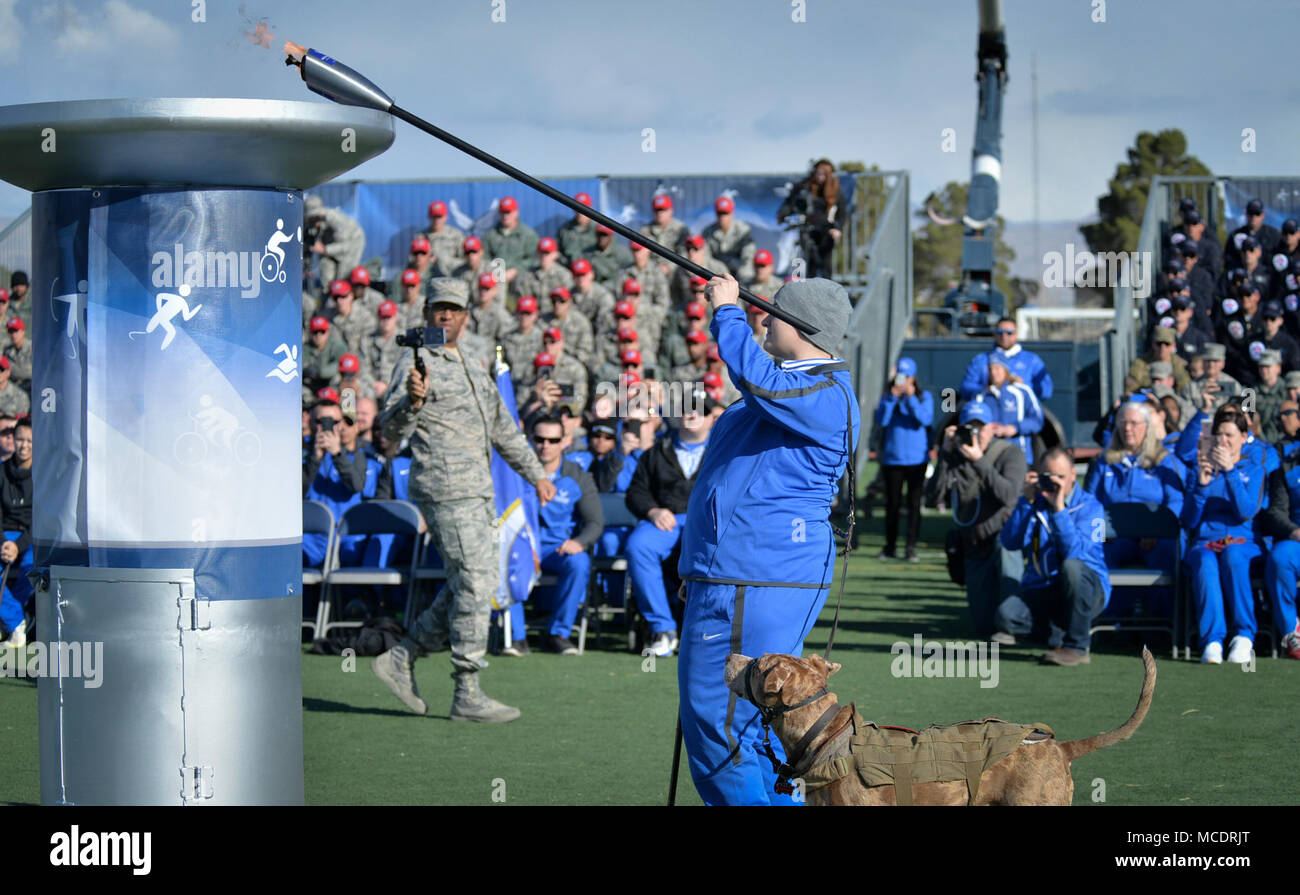 Hanna Stulberg, and Vahalla, her service dog light the cauldron during the Air Force Warrior Games Trials opening ceremony at Nellis Air Force Base, Nevada on Feb. 23, 2018.  Wounded Warrior teams from Australia, United Kingdom, U.S. Army and Air Force will participate in sporting events during the competition.  (U.S. Air Force photo by Lawrence Crespo) - Stock Image