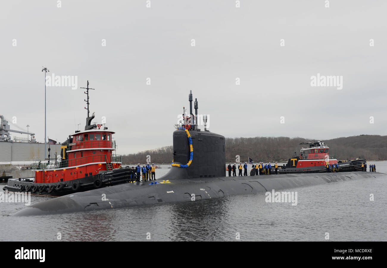 180222-N-LW591-008 GROTON, Conn. (Feb. 22, 2018) Sailors assigned to the Virginia-class, nuclear-powered, fast-attack submarine, USS Virginia (SSN 774) stand topside as their friends and families cheer their arrival as Virginia pulls into its homeport on Naval Submarine Base New London in Groton, Conn., on Thursday 22, Feb. Virginia is returning from the European Command Area of Responsibility where they executed the Chief of Naval Operation's Maritime Strategy in supporting national security interests and Maritime Security Operations. (U.S. Navy photo by Mass Communication Specialist 1st Clas - Stock Image