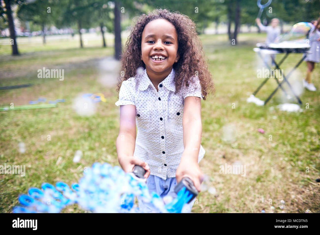 African American Girl Making Soap Bubbles - Stock Image